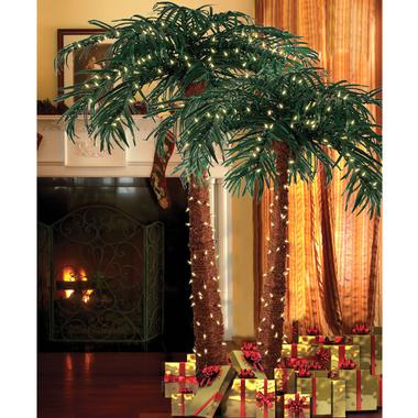 Natural palm trees decorated with Christmas lights and wrapped gifts underneath, on display next to a roaring fireplace