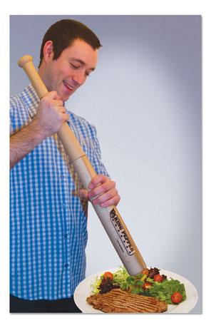 A man grinds pepper on a cooked steak using a full-sized, baseball bat-shaped pepper grinder