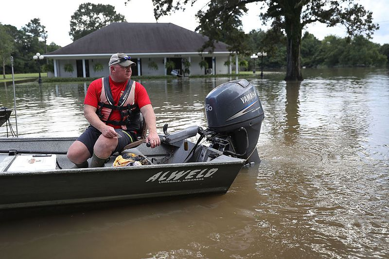 Man in a boat going down a flooded street in Louisiana.
