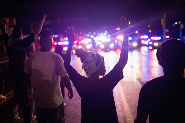 Boy holding hands up before police cars