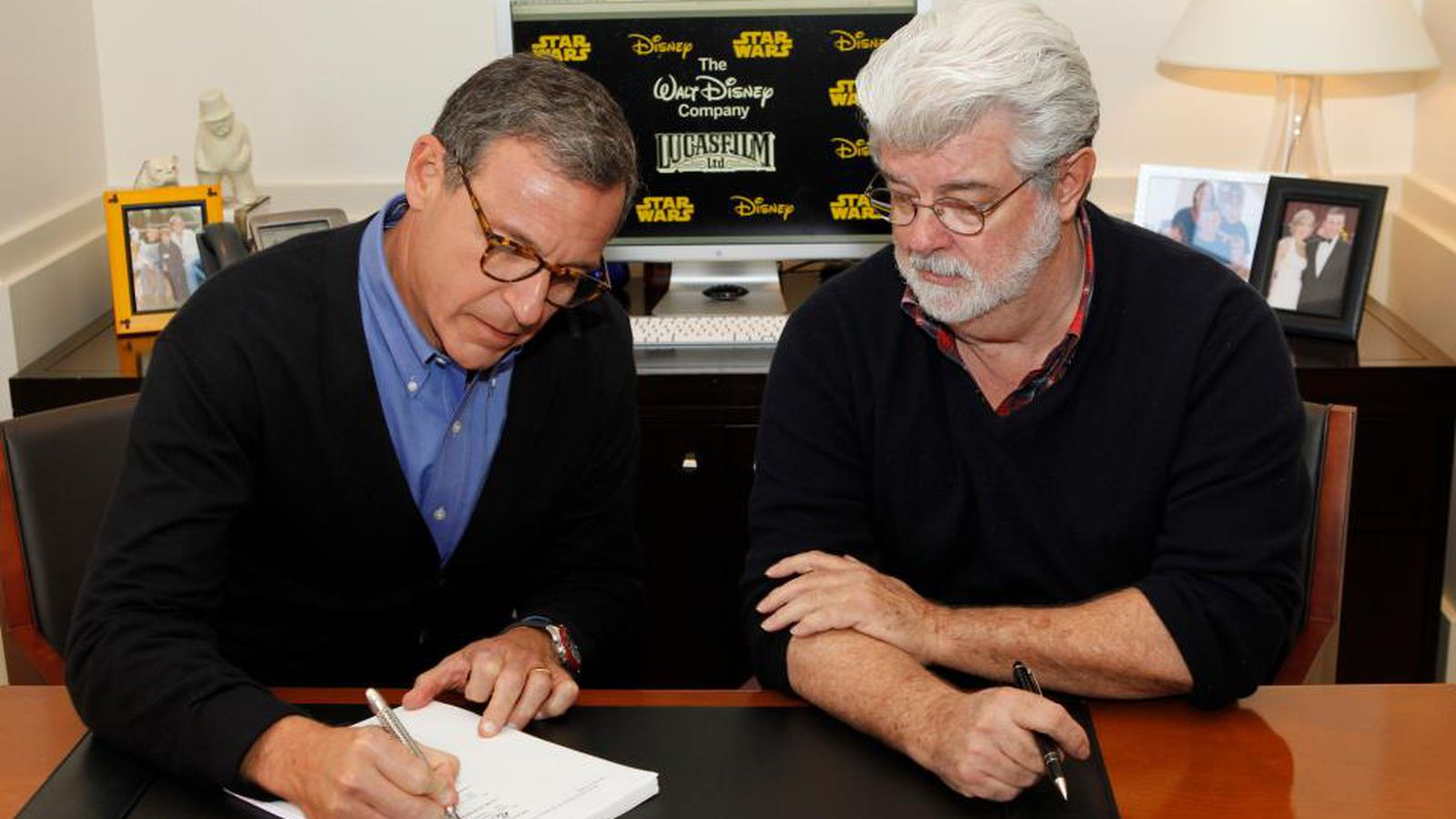 George Lucas and Disney CEO Bob Iger sign the documents that close Lucasfilm's sale