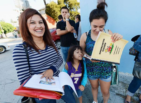 Mitzi Pena, 19 (right), her sister Yaretzi Pena, 5, and her cousin Karina Terriquez, 20 (left), wait in line to receive assistance in filing out their application for the Deferred Action for Childhood Arrivals (DACA) program.