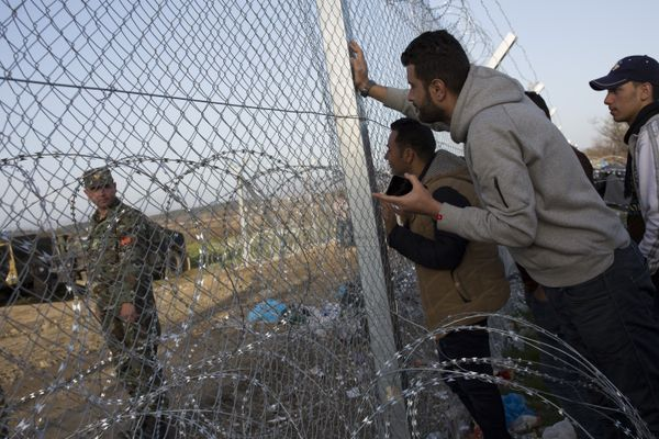 Refugee men talk to a Macedonian soldier along the Greek-Macedonian border.