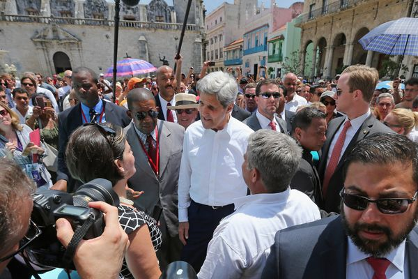 Kerry is surrounded by Cuban and Ameircan security agents; you can see Havana's distinctive architecture in the background.