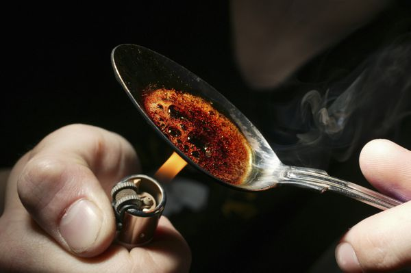 A spoon with heroin being heated up by a cigarette lighter