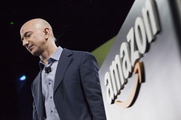 Jeff Bezos at an event announcing the Fire Phone; there is a large Amazon logo in the background