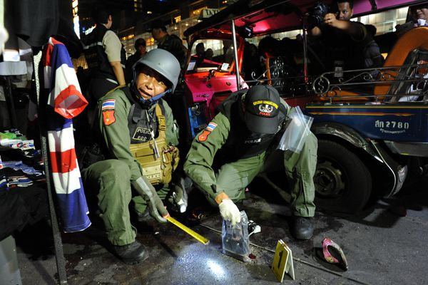 Two police officers, one in a helmet with face visible, the other looking down at a measurement tool.