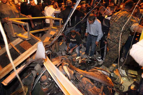 Emergency personnel inspect the debris at the site of the twin suicide bombing near Beirut.