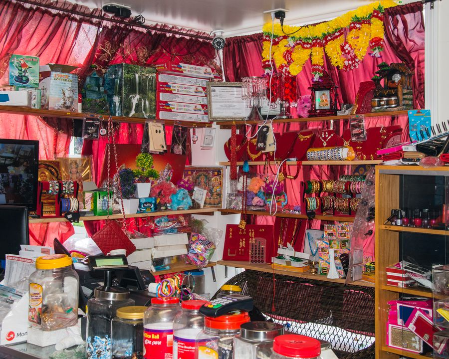 Red fabric covering the windows and shelves stocked very full with merchandise inside of the Nepali Dumpling House.