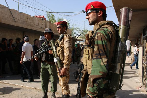 Iraqi soldiers watch as armed tribesmen gather to show their willingness to join Iraqi security forces on June 16, 2014 in Basra,