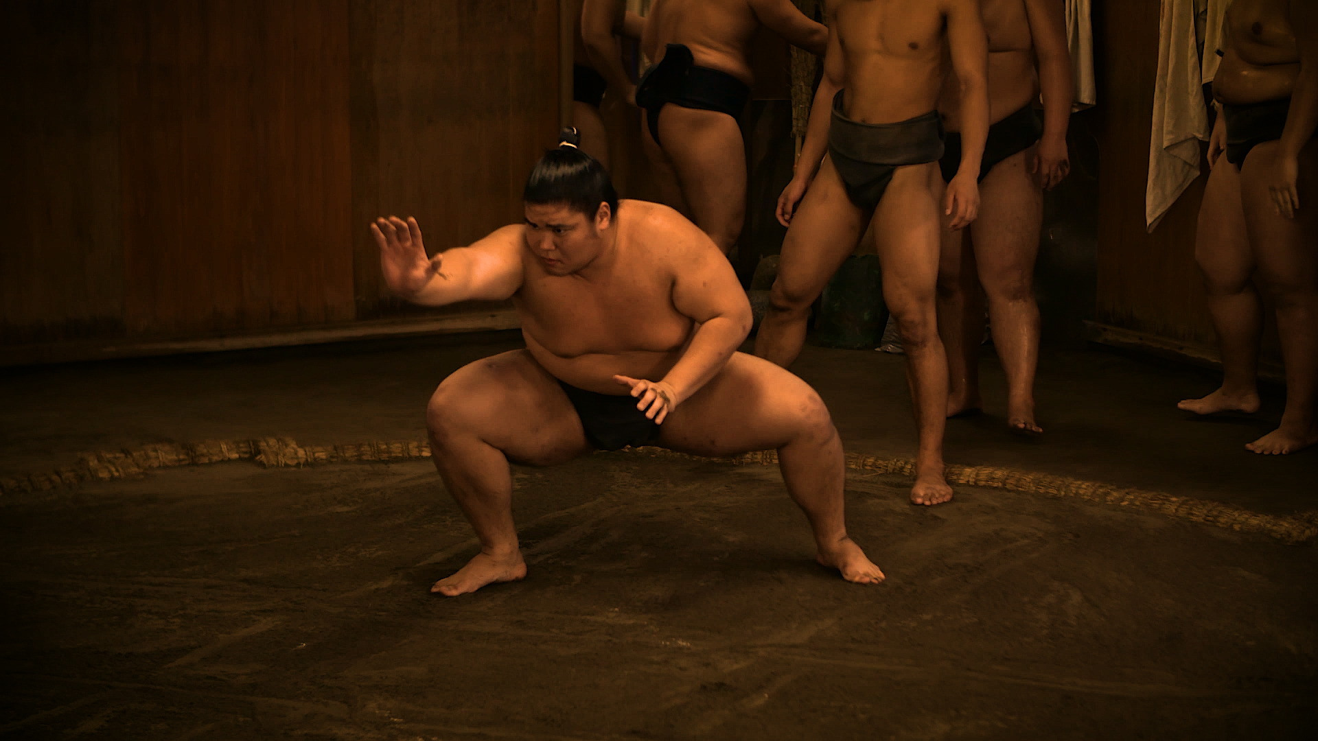 Sumo with his right hand extended