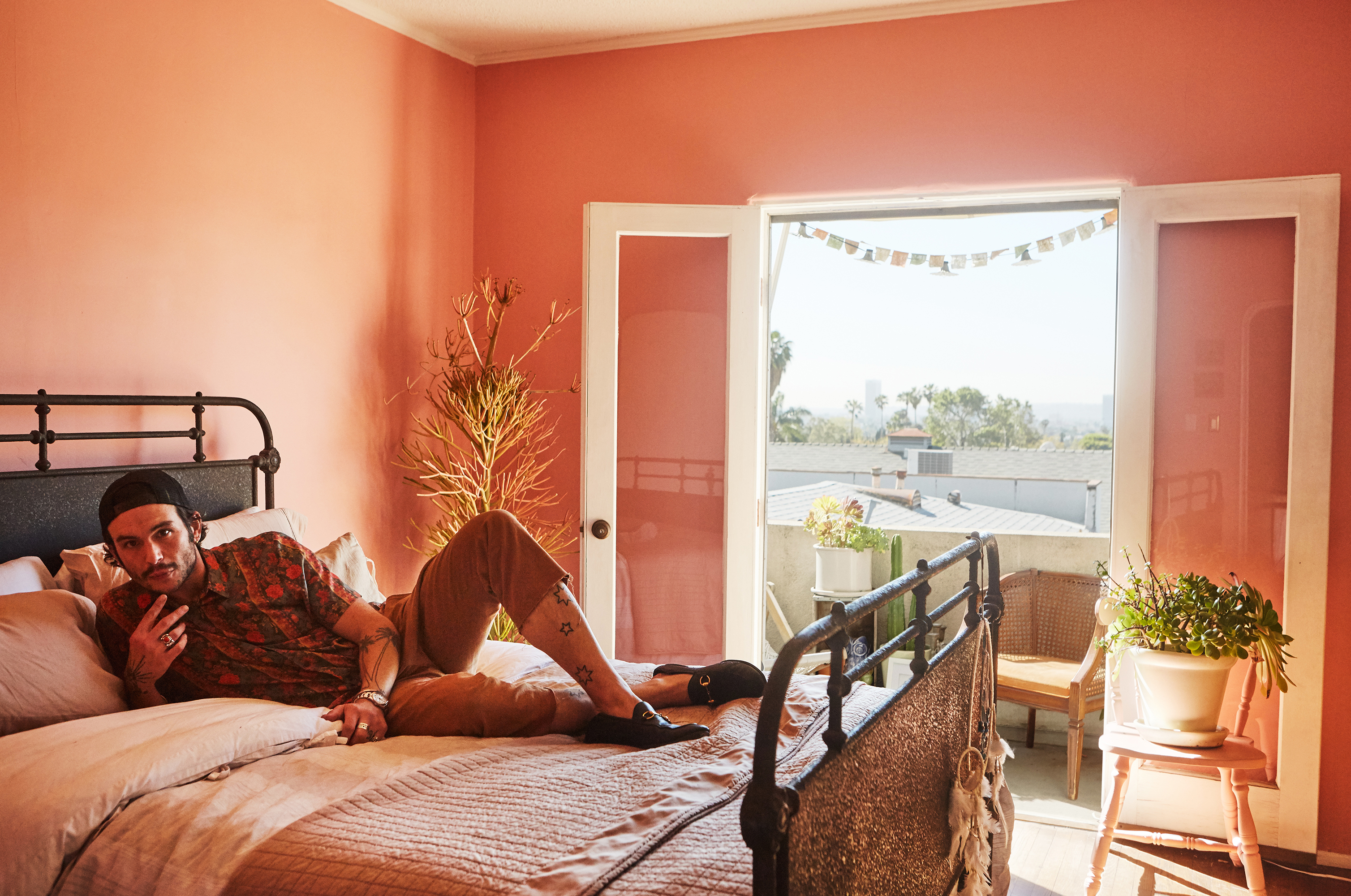 Austin-Paglialonga reclines on his bed in his pink bedroom.